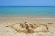 A sand castle on a sunny beach and beautiful clear sea water. Sh