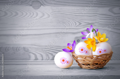 Beautiful flowers and easter eggs basket.