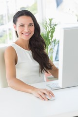 Cheerful businesswoman sitting at her desk