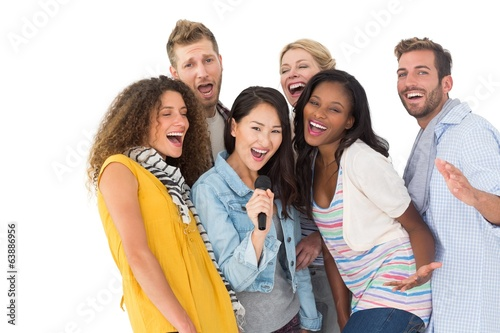 Happy group of young friends having fun doing karaoke
