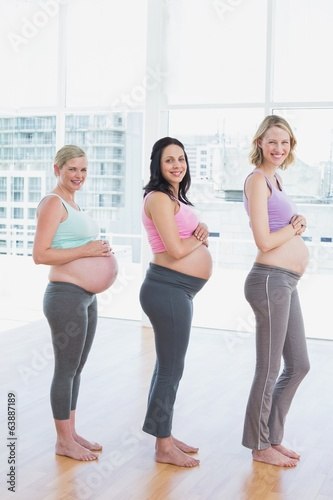 Happy pregnant women standing in a line smiling at camera