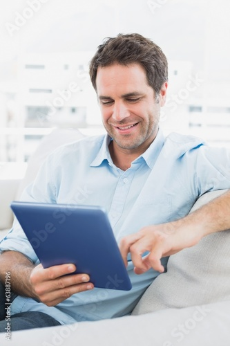 Handsome happy man sitting on the sofa using his tablet pc