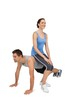Female trainer sitting on man as he does push ups