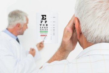 Pediatrician ophthalmologist with senior patient pointing at eye