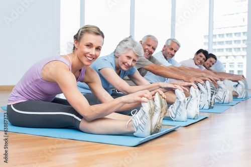 Class stretching hands to legs at yoga class