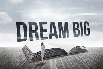 Dream big against open book against sky
