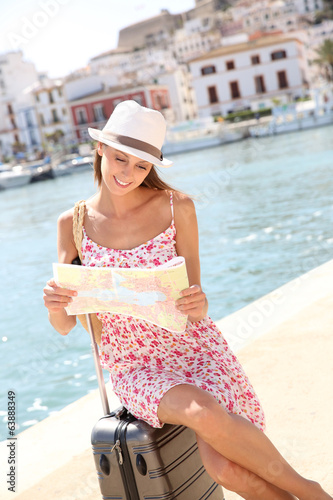 Beautiful girl looking at city map sitting on suitcase