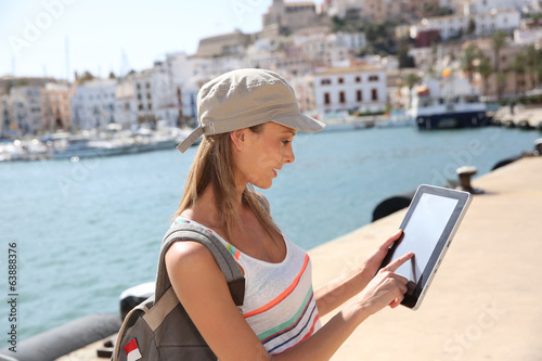 Cheerful tourist girl using digital tablet