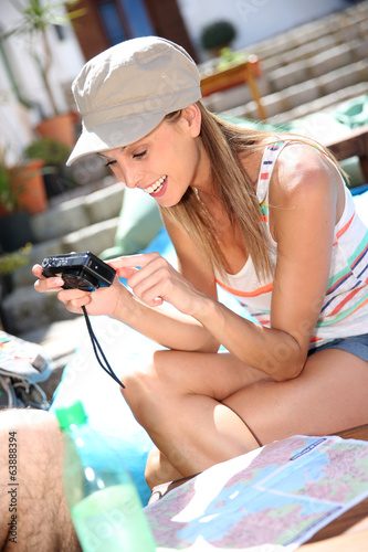 Smiling girl in vacation checking on pictures taken