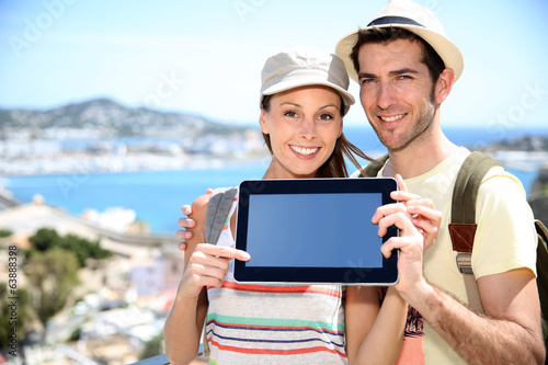 Cheerful couple of travelers showing tablet screen to camera
