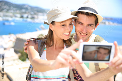 Couple of travelers taking picture of themselves with camera
