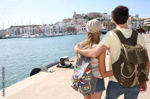 Couple with backpack looking at city of Ibiza from harbour