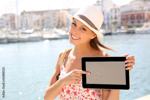 Beautiful tourist girl showing tablet screen
