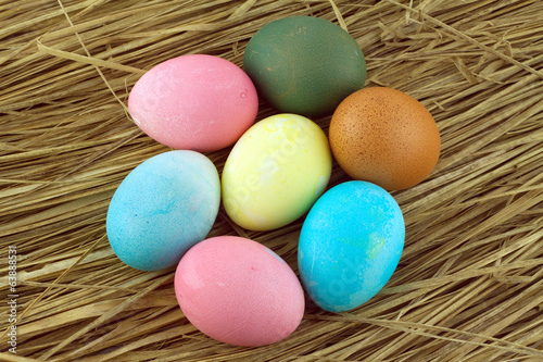 Colorful Easter eggs on straw background closeup
