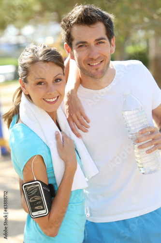 canvas print picture Cheerful couple of joggers looking at camera