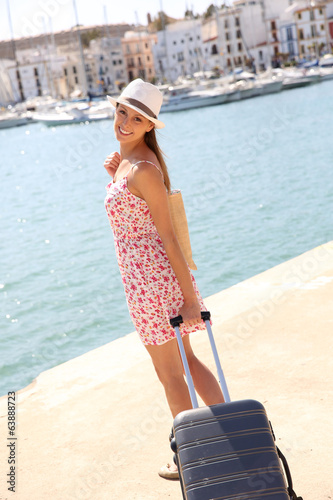 Beautiful fancy girl pulling suitcase on marina