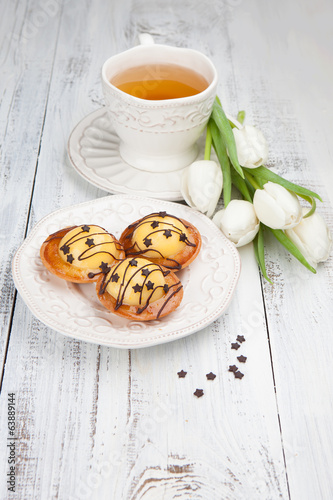 Sweet cake with cup of tea and flowers on white wooden table