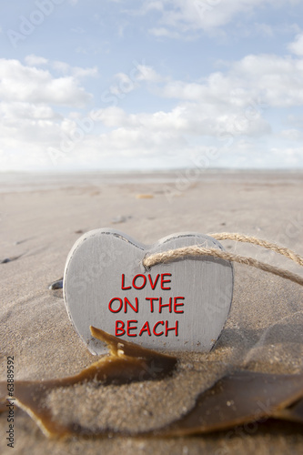 wooden love on the beach heart in the golden sand
