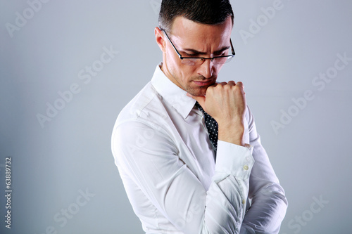Portrait of a pensive man in glasses on gray background