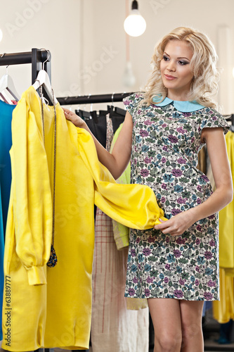 Woman is choosing dress in the shop
