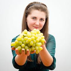 Красивая молодая женщина предлагает виноград