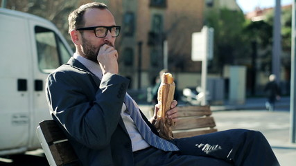 Young handsome businessman eating baguette by the city street