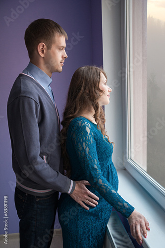 The couple is looking out the window