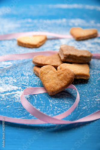 Cookie-hearts on a blue background with a pink ribbon