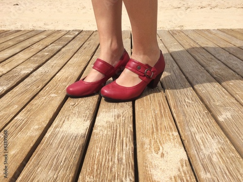 A woman in red shoes in the beach