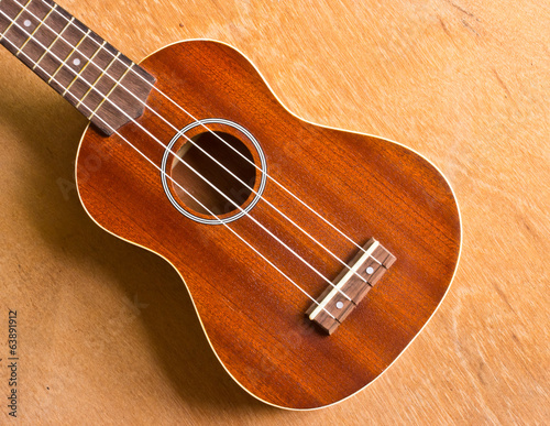 The ukulele is placed on a vintage wooden floor.