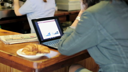 Businesswoman working on laptop computer by counter in bar