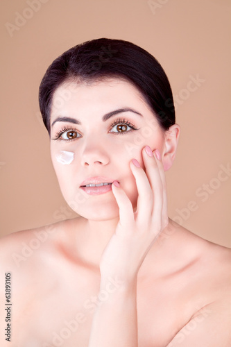 girl with cream on her cheek holds a hand near the face