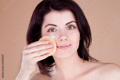 Girl cleans the skin cream with a sponge