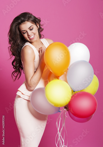 Gorgeous woman with multi colored balloons.