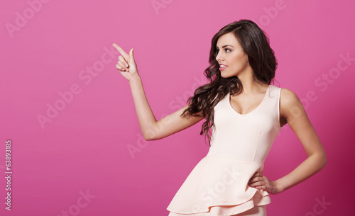 Beautiful woman pointing at copy space