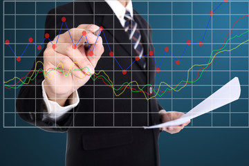 Businessman write growing graph