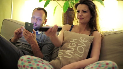 Young couple on sofa watching funny comedy tv at home