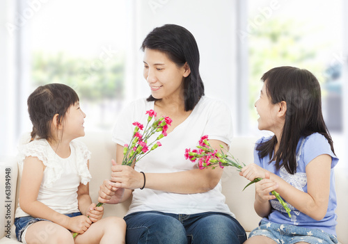 two daughters handing mother carnations