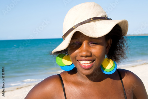 Happy african woman with hat enjoying the sun at the beach.