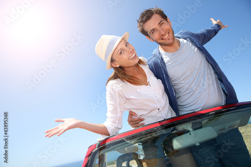 Funny couple with arms up from convertible car