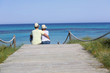 Back view of couple relaxing on beach pontoon