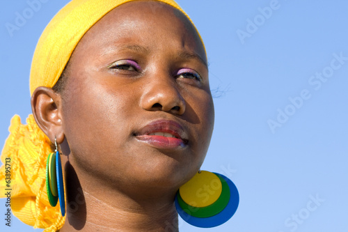 Portrait of young african woman with scarf is looking interested