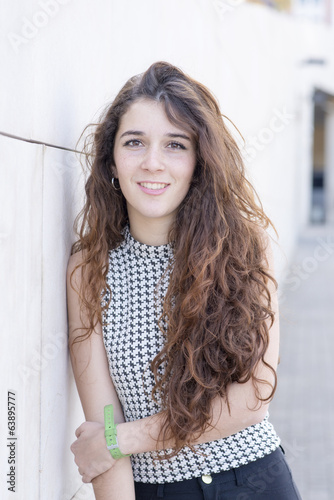 Portrait of smiling young woman with long hair, outdoor.