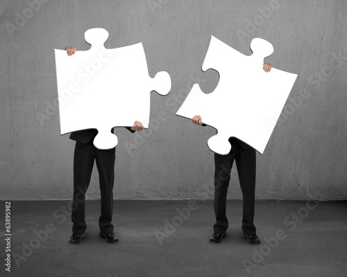 Men holding two puzzles