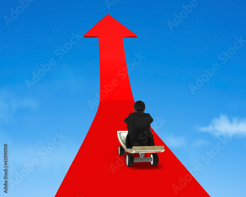 Sitting on money skateboard on growing red arrow