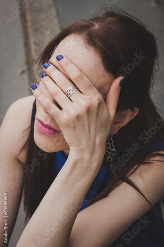 Detail of a girl hiding her face