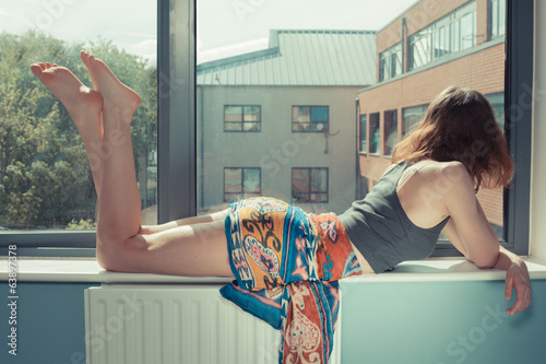 Young woman lying on window sill