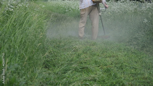dense water dew drops rise worker with trimmer mow wet grass