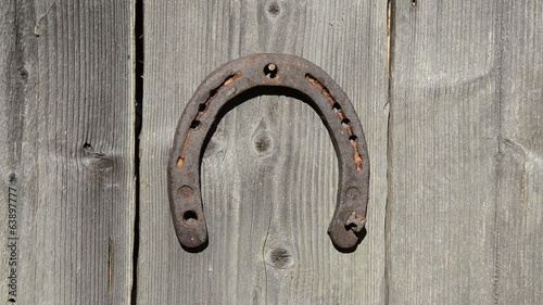 woman hand bracelet hang rusty horse shoe on wooden house wall