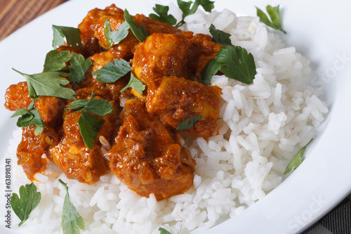 Chicken breast curry with rice on a white plate